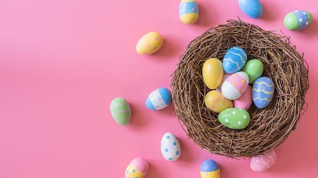 Красочные пасхальное яйцо и гнездо на розовый пастельный цвет фона с пространством.