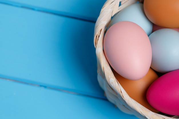Colorful easter egg in the basket on blue wood wall with space.