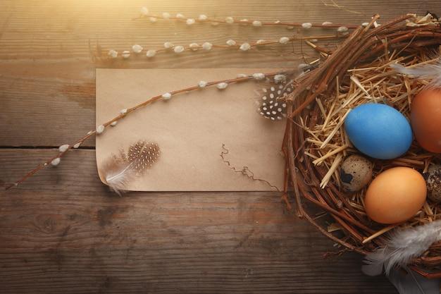 어두운 나무 보드에 둥지에서 다채로운 부활절 달걀.