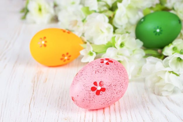 다채로운 부활절 달걀과 흰색 나무 테이블에 꽃 지점