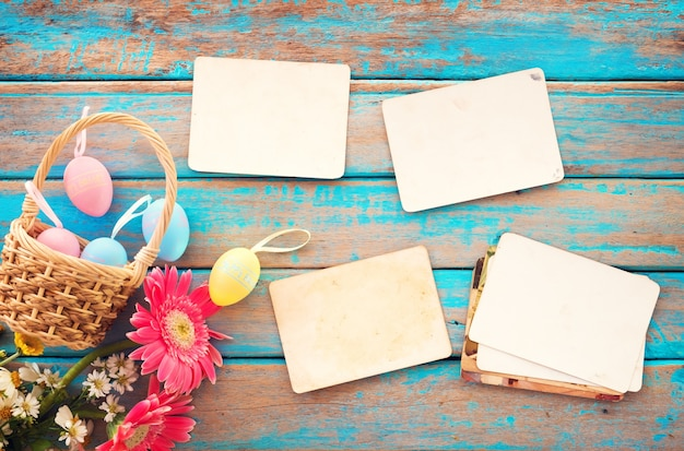 カラフルなイースターエッグと空の古い紙の写真アルバムの木のテーブル