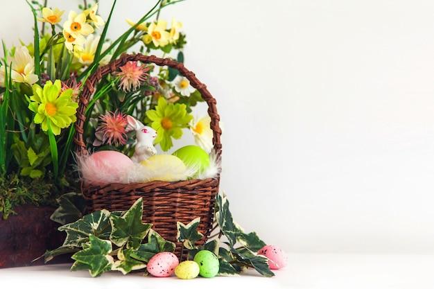 カラフルなイースターの卵とバスケットに小さな白いウサギと花。