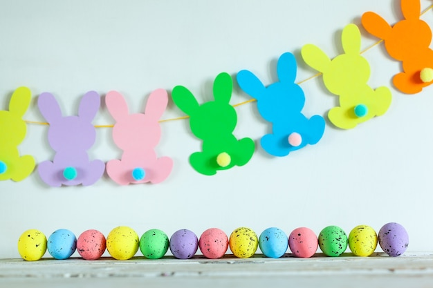 Красочные пасхальные яйца и пасхальная гирлянда кролика ручной работы на бежевом фоне. счастливой пасхи концепции.