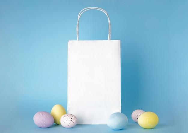 Красочные пасхальные яйца и бумажный пакет на голубой поверхности, место для текста.