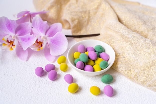 다채로운 부활절 달걀과 흰색 책상에 접시와 호 접 난초 꽃.