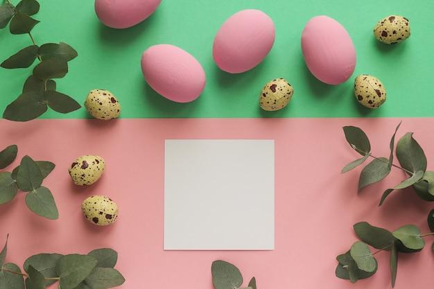 空の紙の空白と幾何学的なピンクと緑のテーブルにカラフルなイースターエッグとウズラの卵