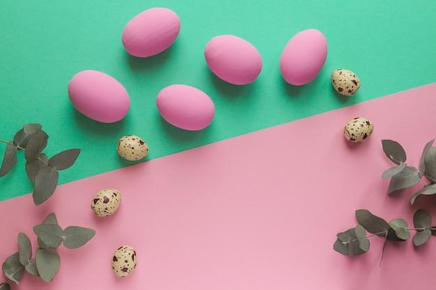 ユーカリの葉と幾何学的なピンクと緑のテーブルにカラフルなイースターエッグとウズラの卵