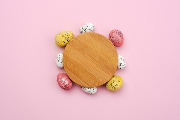 ピンクの背景に木製のスタンドの周りのカラフルなイースターエッグ
