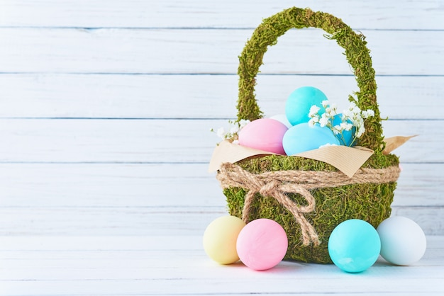 Colorful easter eggs in backet on a white wooden background