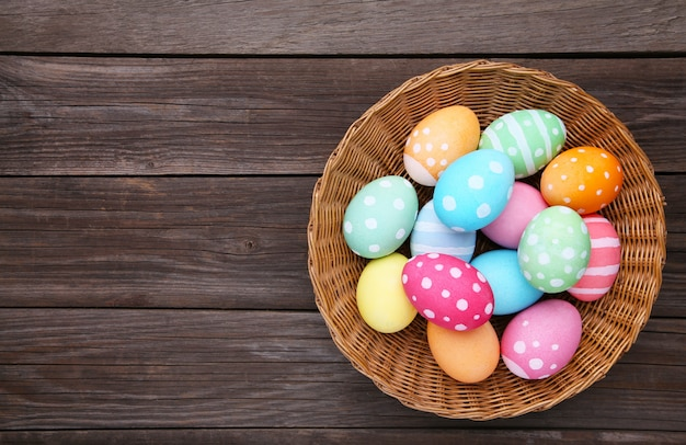 Colorful easter eggs in basket on grey wooden table, top view