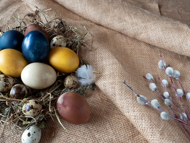 Colorful easter eggs and bouquets on a coarse cloth