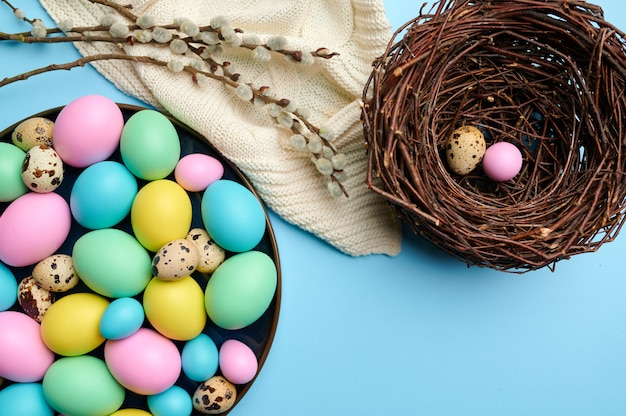 Colorful easter eggs in bowl and decorative nest on blue background, top view
