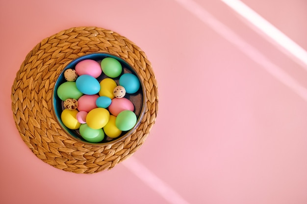 Colorful easter eggs in bowl, pink background, top view