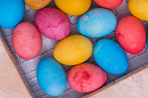 Colorful easter eggs in box on table