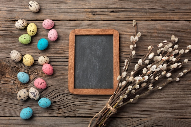 Colorful easter eggs and brushes on wooden table. top view with copy space.