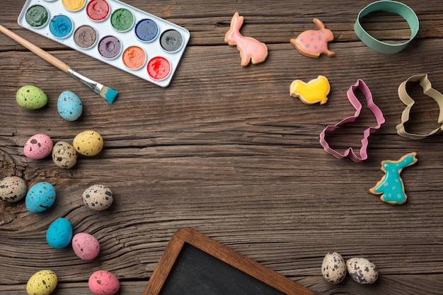 Colorful easter eggs and brushes on wooden table. top view with copy space