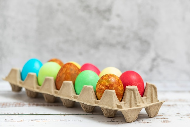 Colorful easter eggs in a cardboard egg box on light.