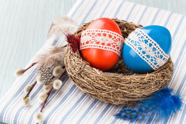 Colorful easter eggs decorated with lace in small nest, willow branch. easter concept.