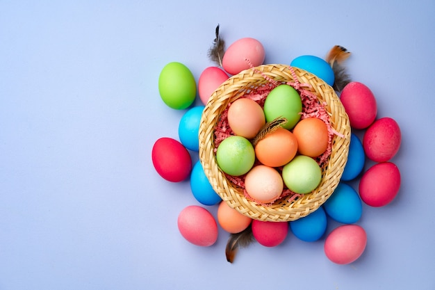 Colorful easter eggs in decorative nest on blue background