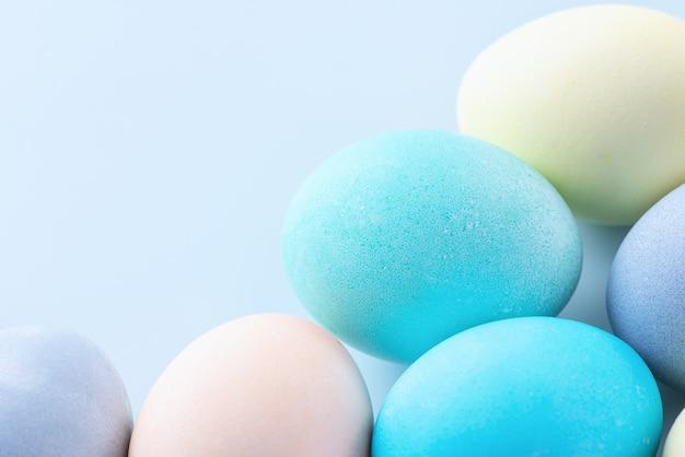 淡いブルーの背景に分離された色の水で染められたカラフルなイースターエッグ、イースター休暇の活動のデザインコンセプト、クローズアップ、コピースペース。