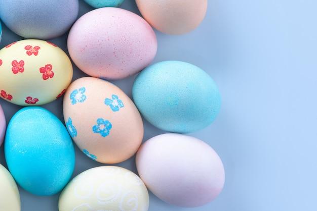 淡いブルーの背景に美しい模様の色の水で染められたカラフルなイースターエッグ、休日の活動のデザインコンセプト、上面図、コピースペース。