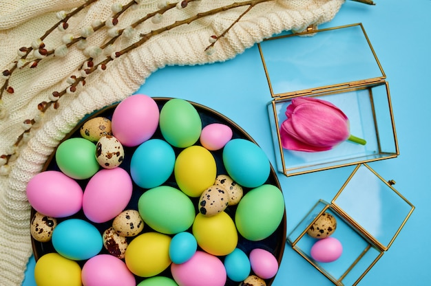 Colorful easter eggs and floral decoration on blue background