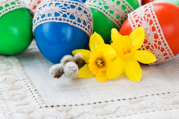 Colorful easter eggs and fresh narcissus on white tablecloth. easter background, copy space.