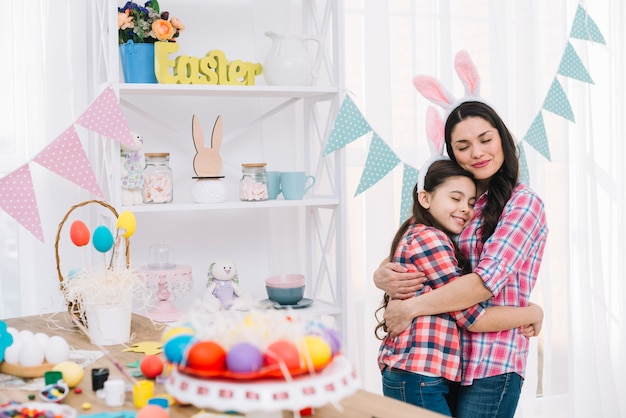Colorful easter eggs in front of mother and daughter embracing each other