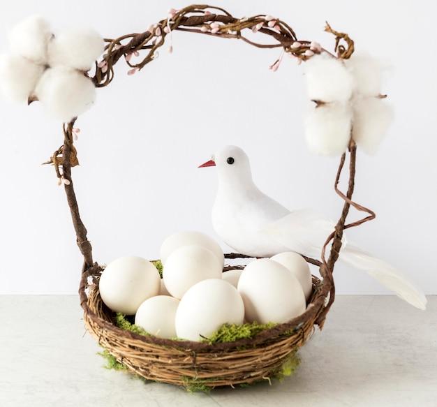 Uova di pasqua colorate nel cesto di fieno vista frontale
