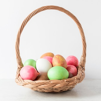 Colorful easter eggs in hay basket front view