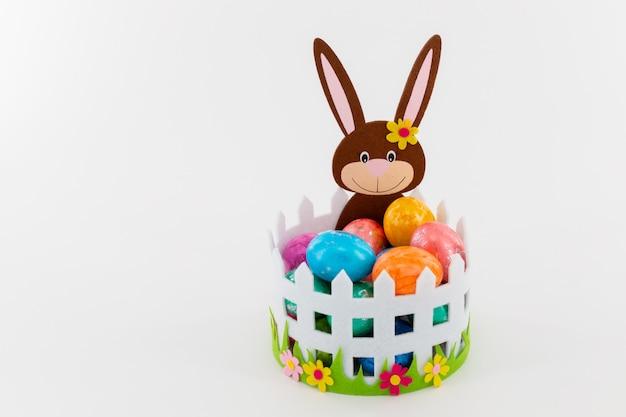 イースターのウサギが付いているバスケットのカラフルなイースターエッグ
