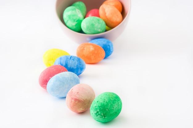 Красочные пасхальные яйца в миску на белом фоне