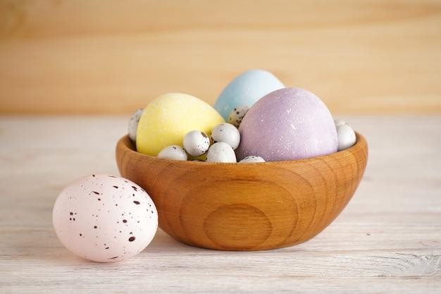 Красочные пасхальные яйца в деревянной миске на деревянном фоне