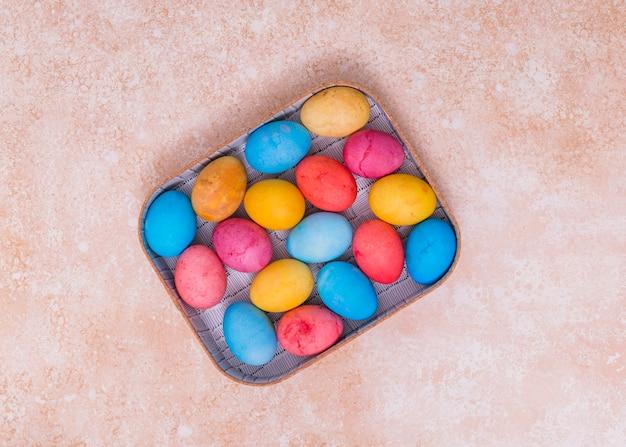 베이지 색 테이블에 상자에 다채로운 부활절 달걀