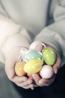 子供の手のカラフルなイースターエッグ、ソフトフォーカスと色調。イースターコンセプトの背景。