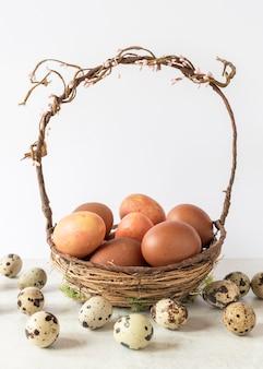 Красочные пасхальные яйца в корзине сена вид спереди