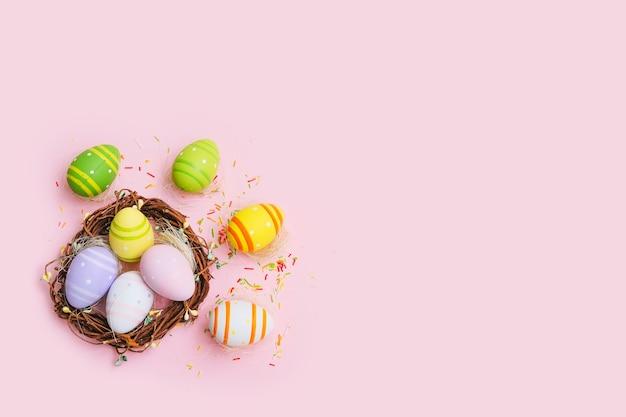 Красочные пасхальные яйца в гнезде на пастельно-розовом столе.