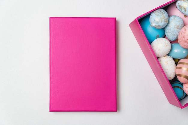 흰색 바탕에 분홍색 사각형 상자에 다채로운 부활절 달걀. 행복한 부활절. 공간을 복사하십시오.