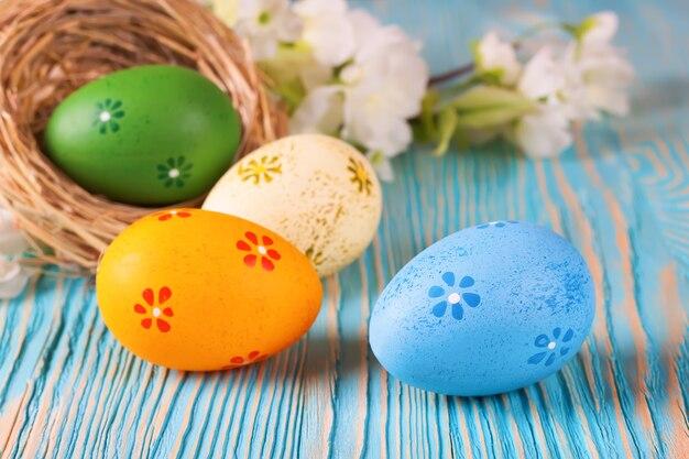 푸른 나무 테이블에 꽃 짚 둥지와 지점에 다채로운 부활절 달걀