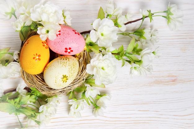 짚 둥지와 흰색 나무 테이블에 꽃 지점에 다채로운 부활절 달걀. 평면도, 평면 누워.