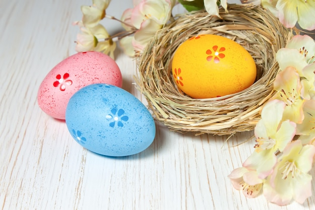 흰색 나무 테이블에 꽃 짚 둥지와 지점에 다채로운 부활절 달걀