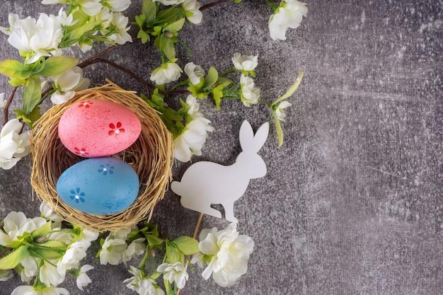 밀짚 둥지와 흰 토끼와 꽃이 만발한 지점에 다채로운 부활절 달걀