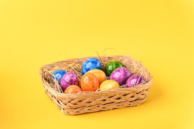 노란색 배경에 바구니에 다채로운 부활절 달걀