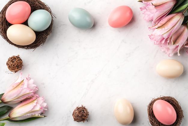 밝은 대리석 흰색 테이블 배경에 분홍색 백합 꽃과 둥지에 다채로운 부활절 달걀. 프리미엄 사진