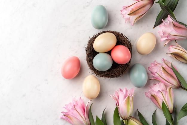 밝은 대리석 흰색 테이블 배경에 분홍색 백합 꽃과 둥지에 다채로운 부활절 달걀.