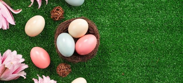 잔디 잔디 배경에 핑크 백합 꽃과 둥지에 다채로운 부활절 달걀.