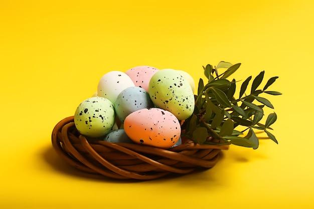 明るい黄色の背景に籐の巣のカラフルなイースターエッグ。