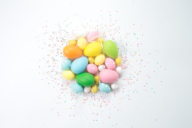 カラフルなイースターの卵は明るい背景に横たわっています。