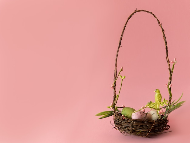 Colorful easter eggs in little basket isolated on pink background.