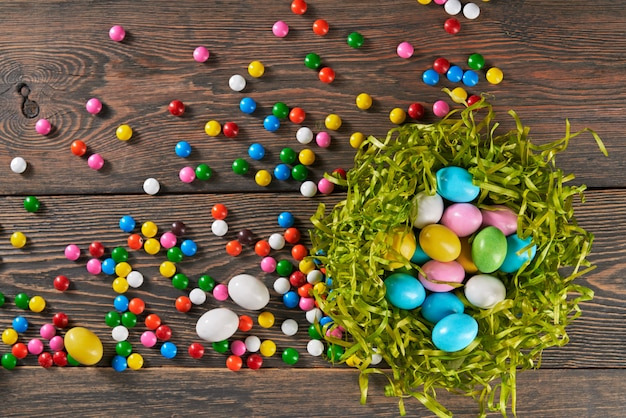 Colorful easter eggs in nest and candies.